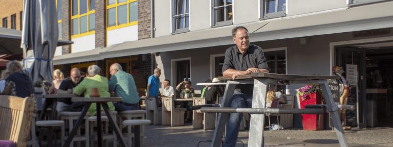 Andreas Tietze sitzt an einem Tisch vor einem Fischrestaurant in Husum