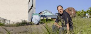 Andreas Tietze sitzt im Gras am Husumer Hafen