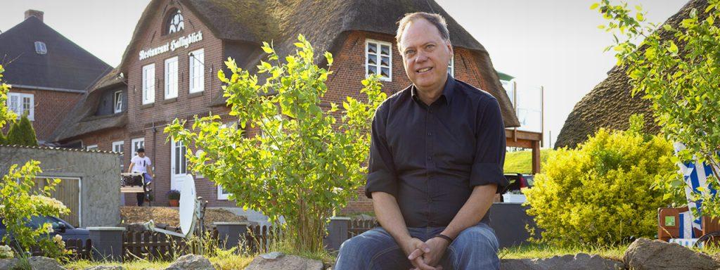 Andreas Tietze sitzt am Deich auf einem kleinen Friesenwall