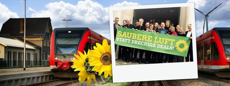 """Fraktion der Grünen in SH mit Transparenz """"Saubere Luft statt dreckiger Deals"""". E-Züge im Hintergrund"""